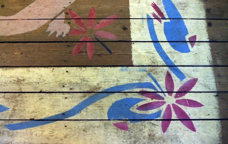 Een detail van het gesjabloneerde vloerkleed